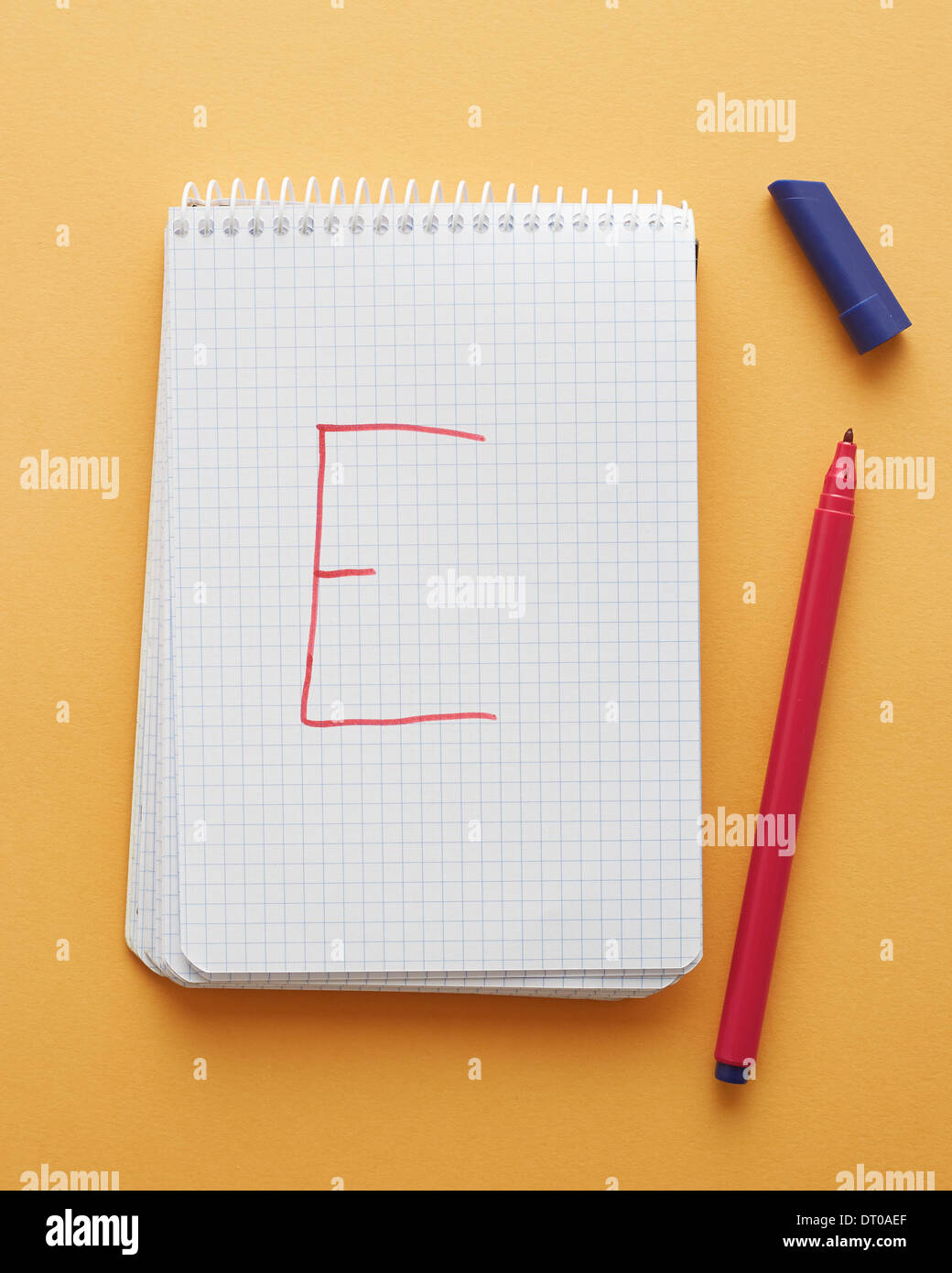E letter handwritten in notebook page on yellow background alphabet - Stock Image