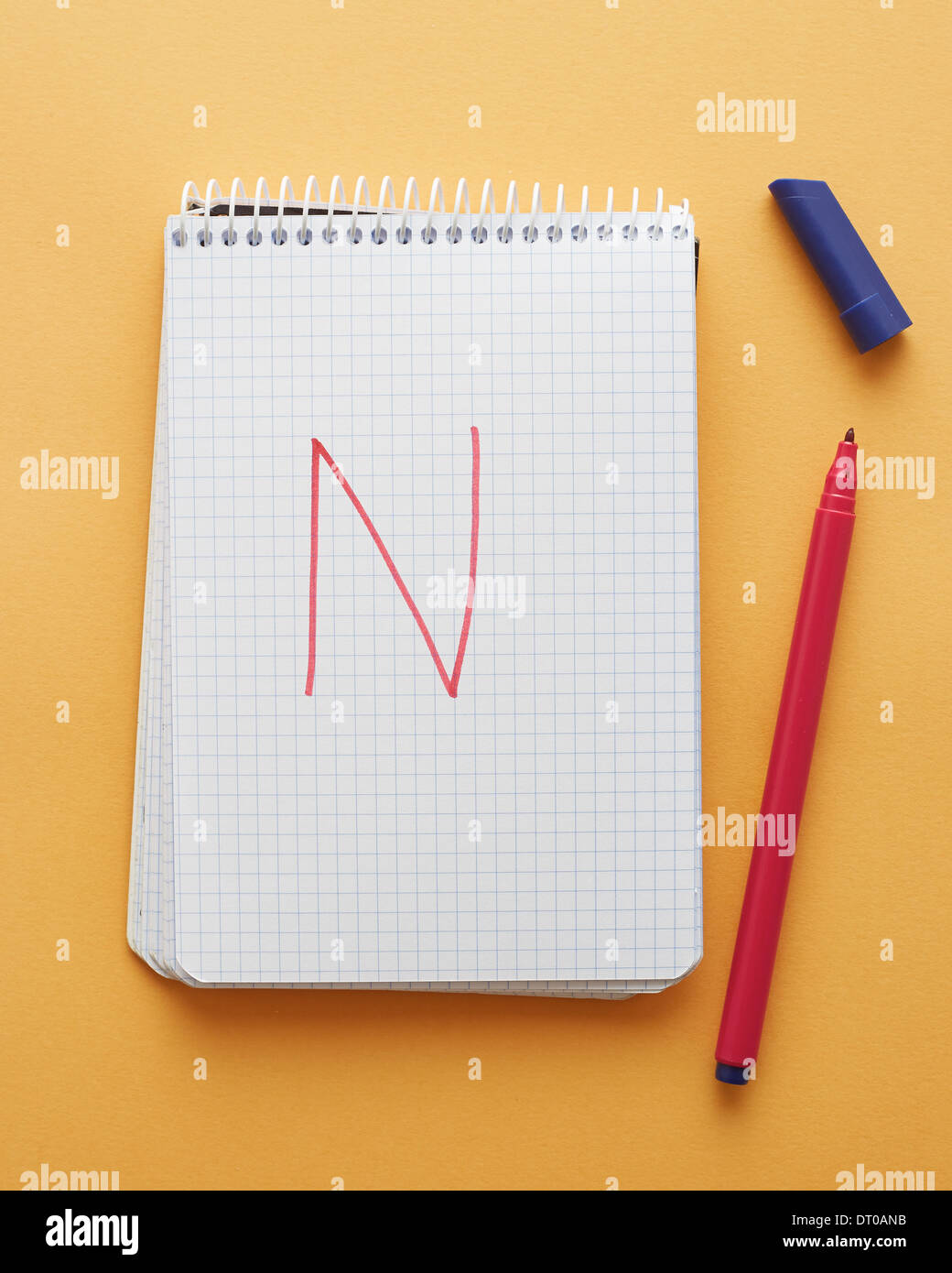 N letter handwritten in notebook page on yellow background alphabet - Stock Image