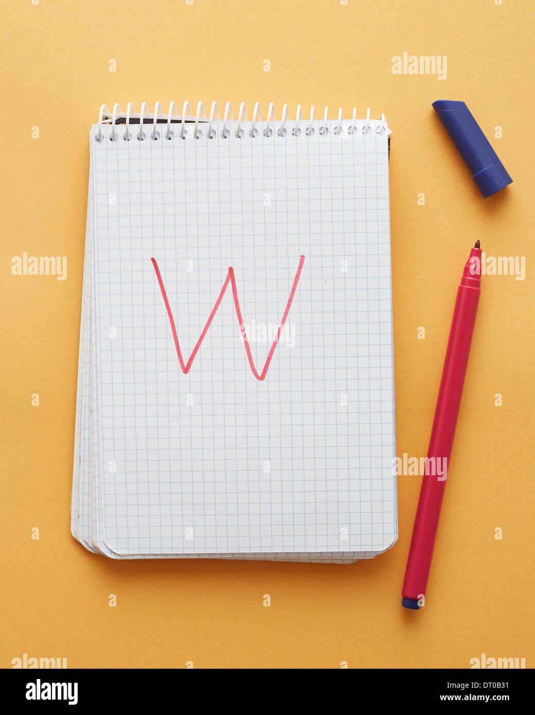 W letter handwritten in notebook page on yellow background alphabet - Stock Image