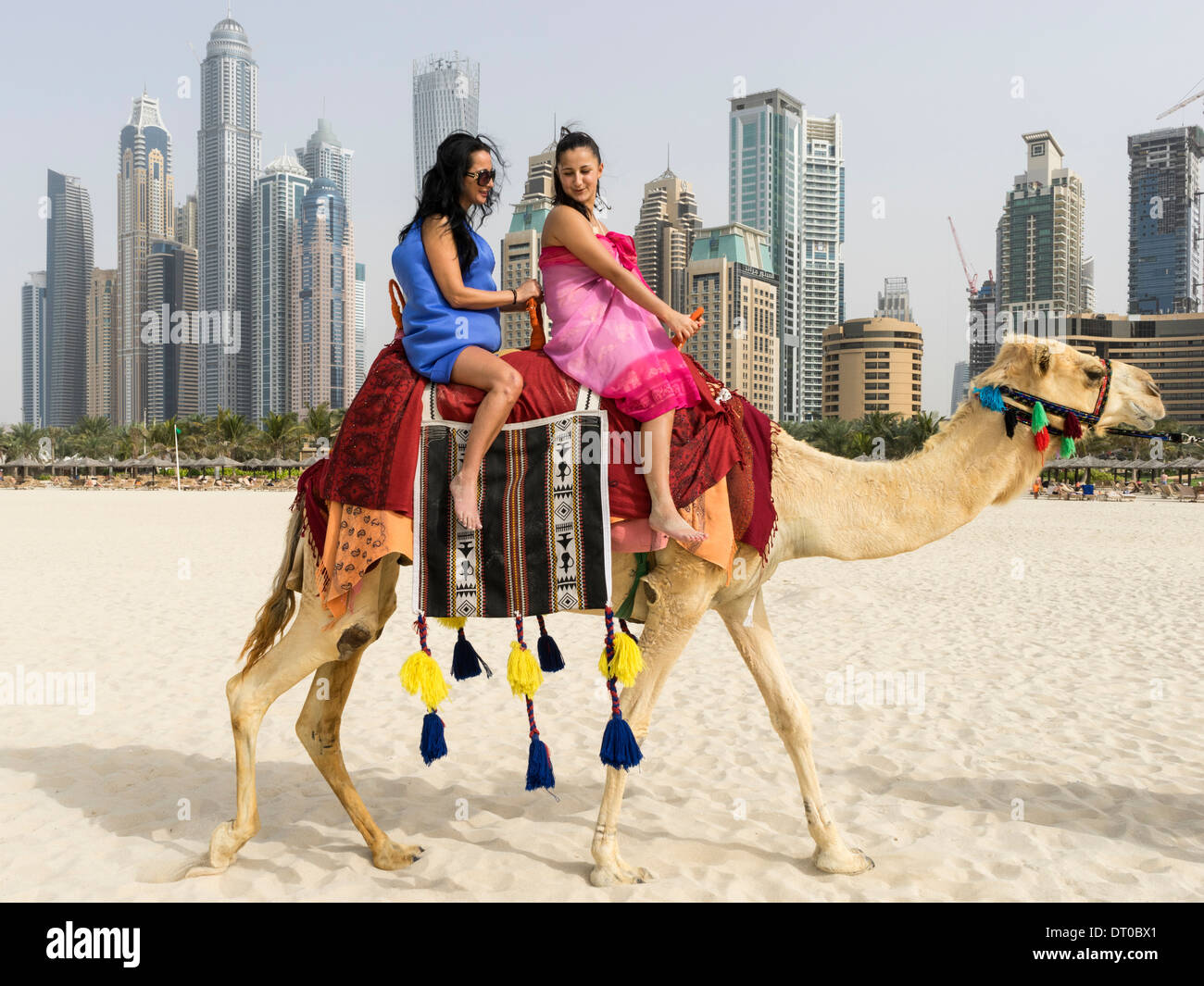 Tourists taking a camel ride on beach at marina district of new tourists taking a camel ride on beach at marina district of new dubai in united arab emirates altavistaventures Choice Image