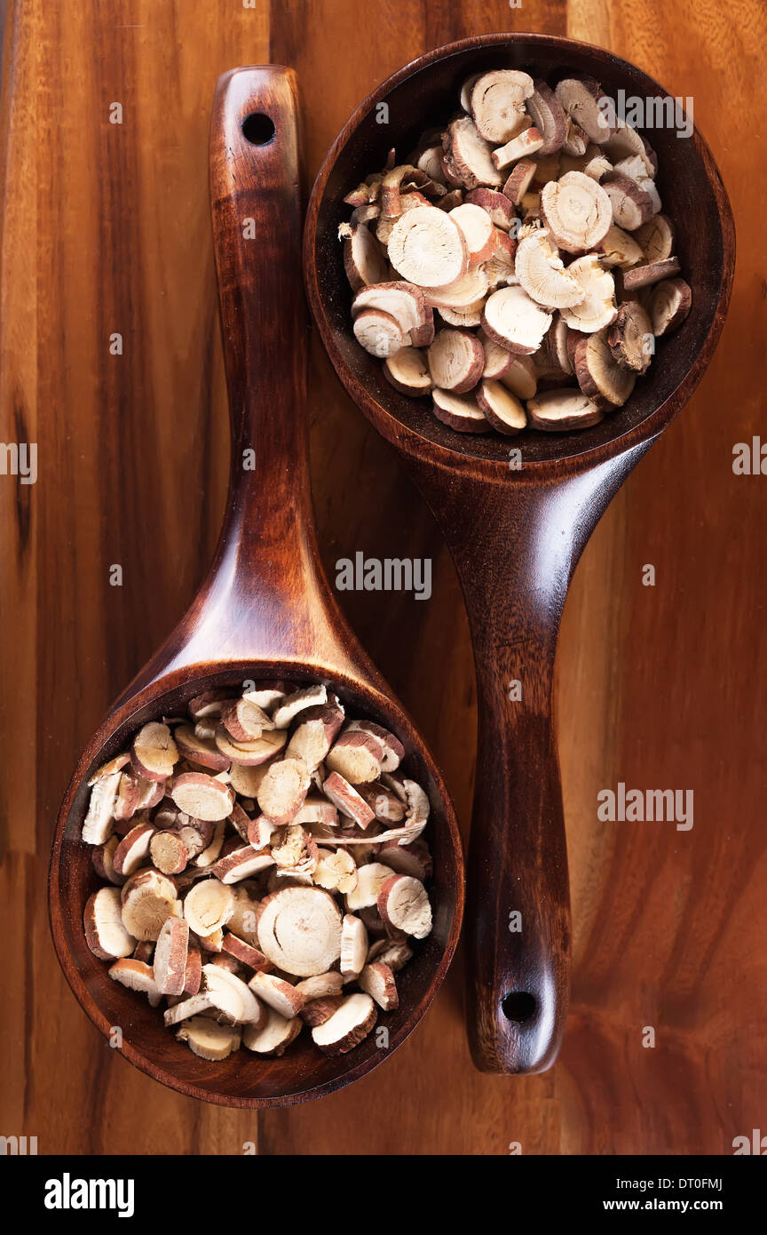 Chopped licorice root on the wooden spoon - Stock Image