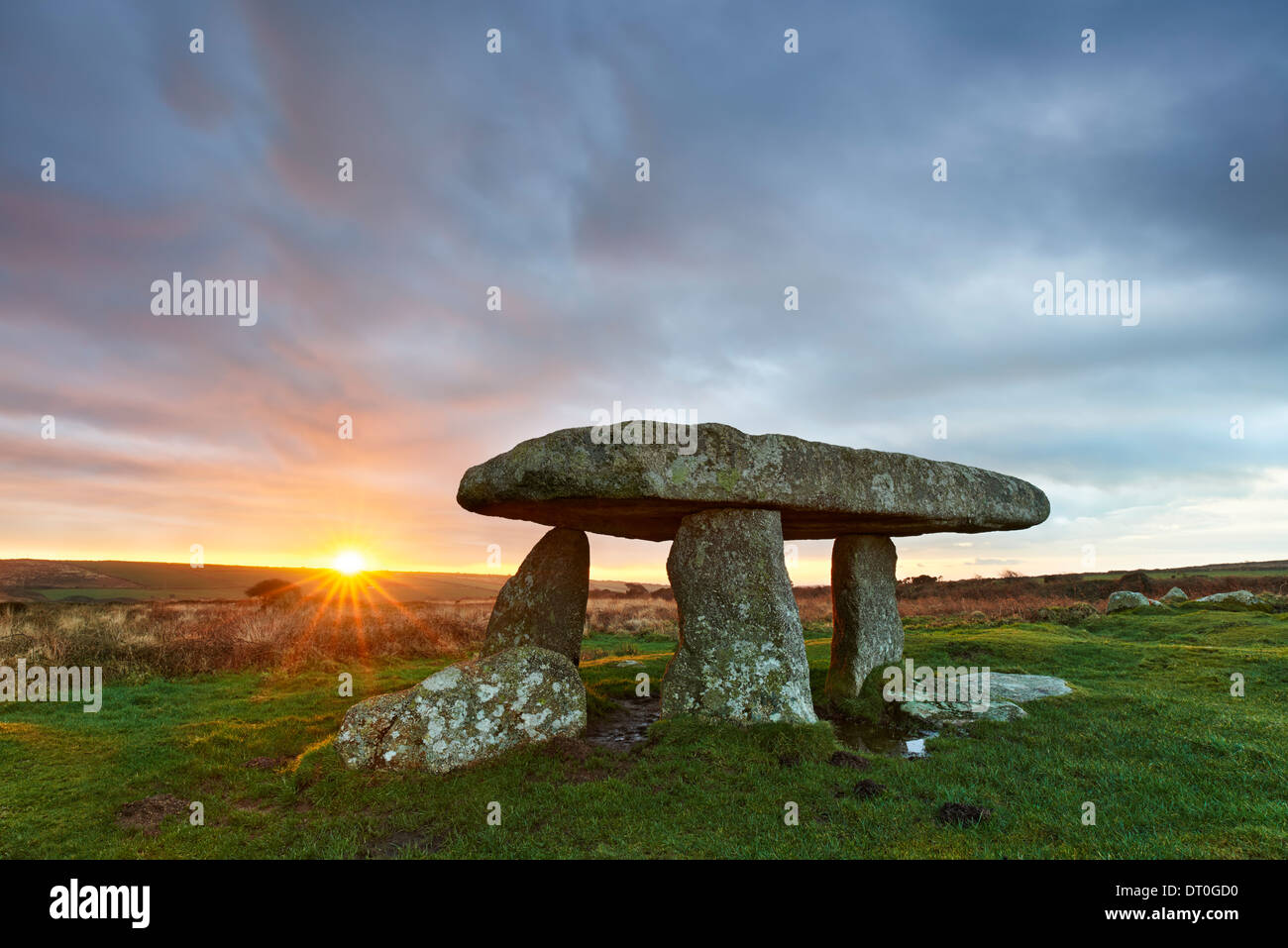 A brief moment of sunlight streaking across the dawn sky at Lanyon Quoit - Stock Image