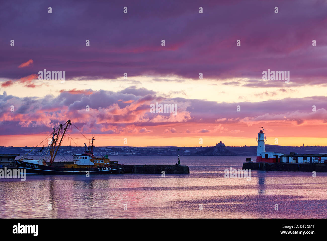 A colourful sky above Newlyn Harbour and Mounts Bay beyond Stock Photo