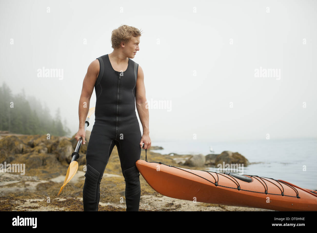 New York state USA man wetsuit kayak onto the shore in misty weather - Stock Image