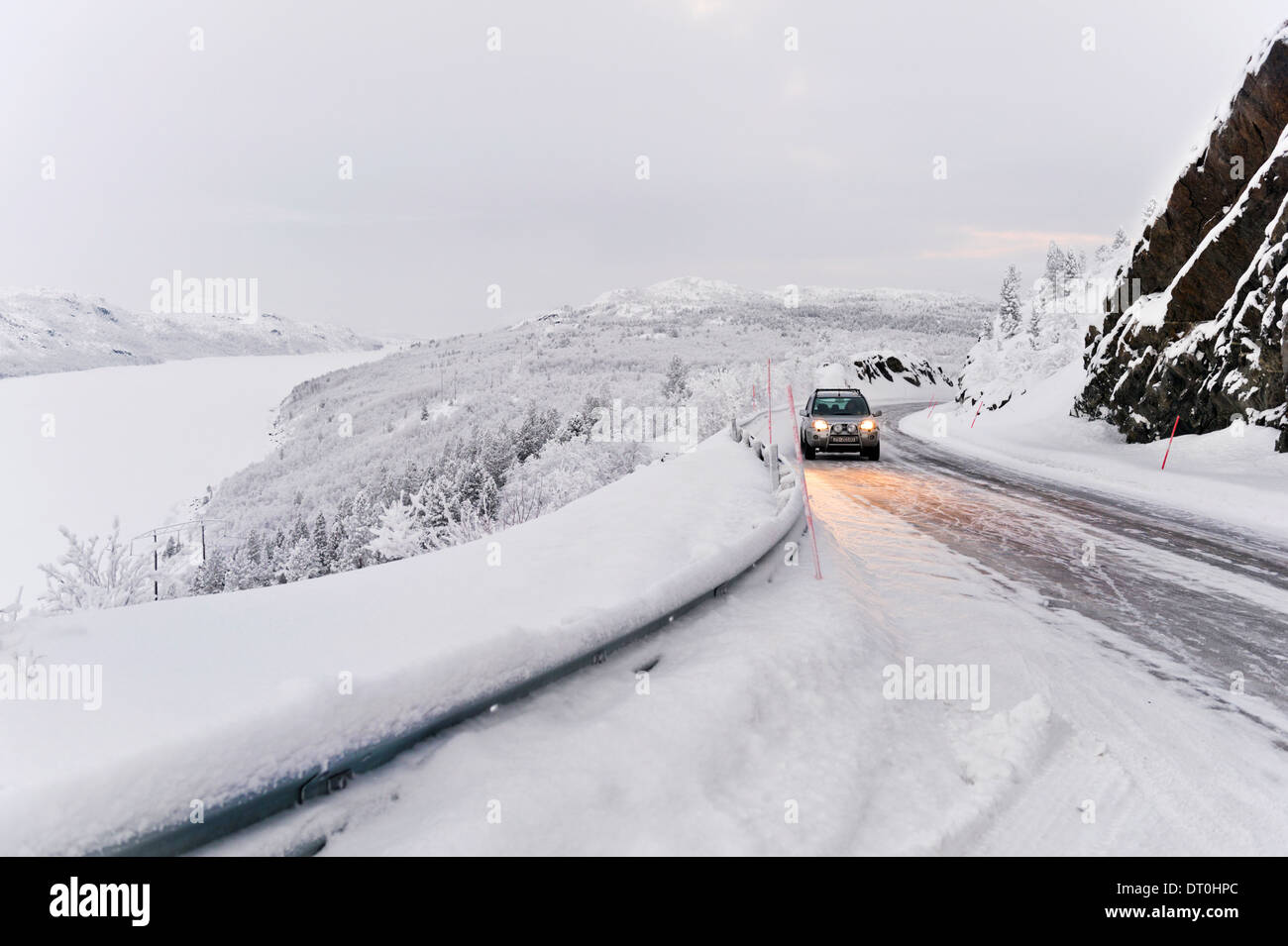 Snow covered Winter road and frozen fjord near Kirkenes, Finnmark, Norway - Stock Image