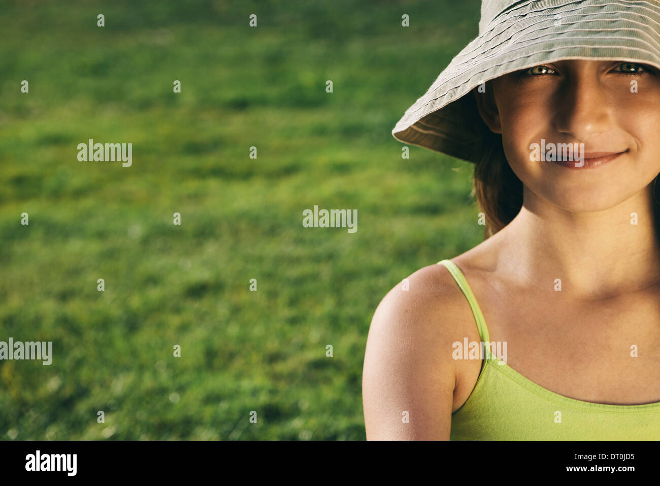 Seattle Washington USA smiling nine year old girl sitting on the grass - Stock Image
