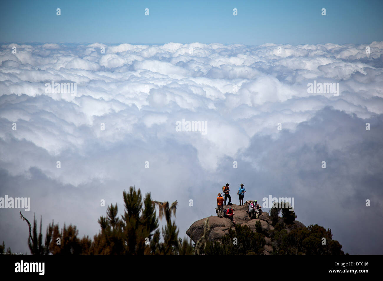 climbers enjoying the above the clouds view on Mount Kilimanjaro - Stock Image
