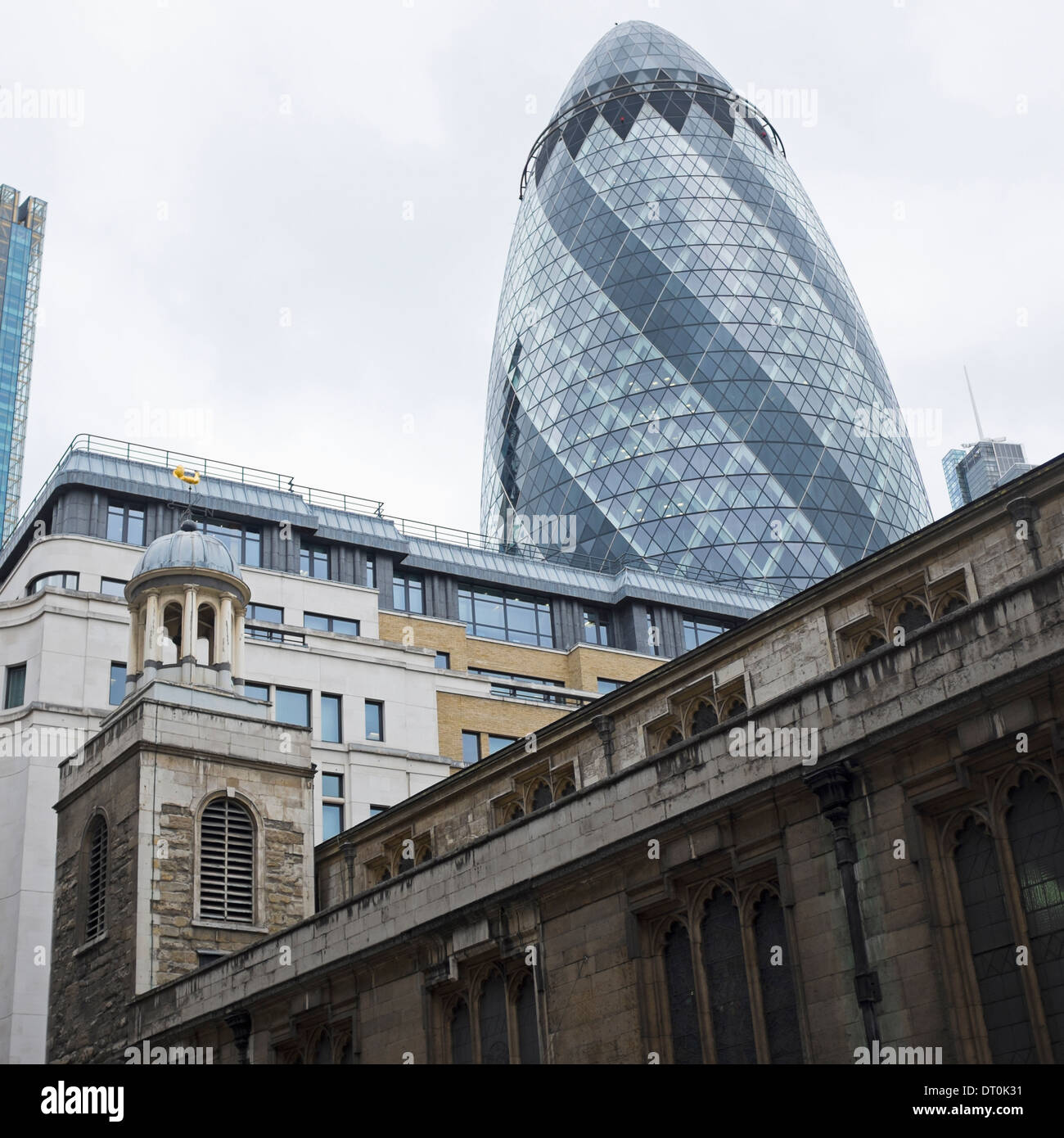 St Katharine Cree church in the foreground with the Swiss RE The Gherkin towering in the background. - Stock Image