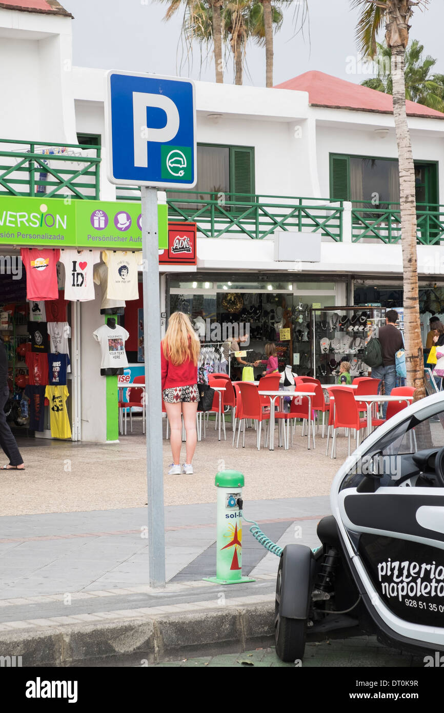 Renault Twizy battery-powered electric car for pizza delivery plugged in to a Sol-lar battery charging point on roadside. - Stock Image