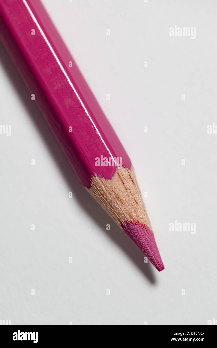 A colored pencil on a white paper background. - Stock Image