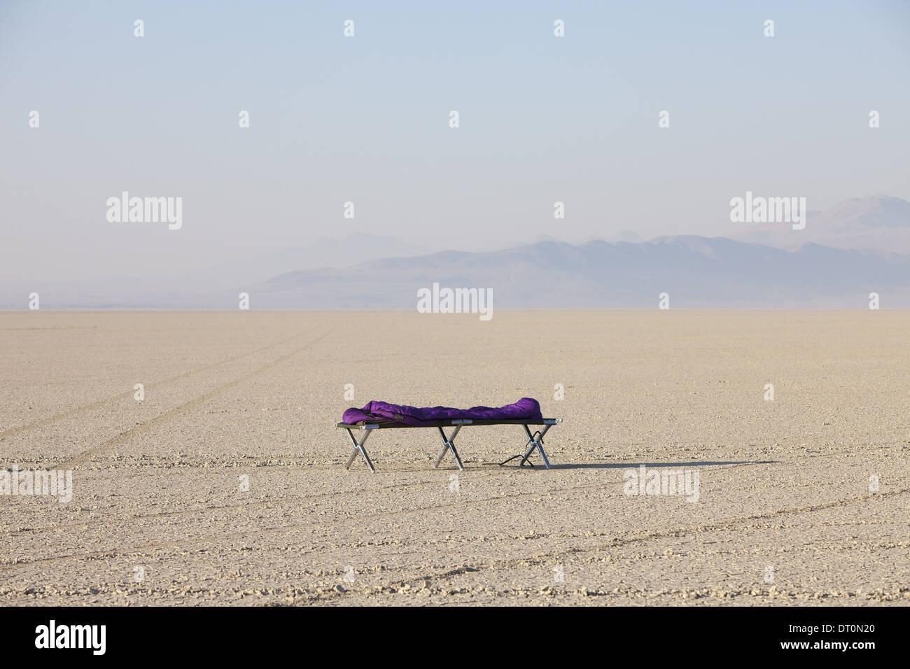 Black Rock Desert Nevada USA Sleeping bag on cot in vast barren desert dawn - Stock Image