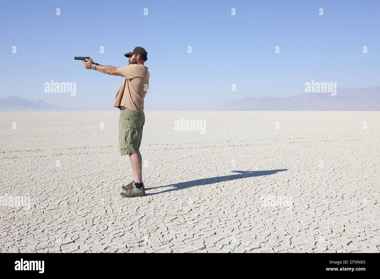 Black Rock Desert Nevada USA man aiming hand gun with his arm outstretched Stock Photo