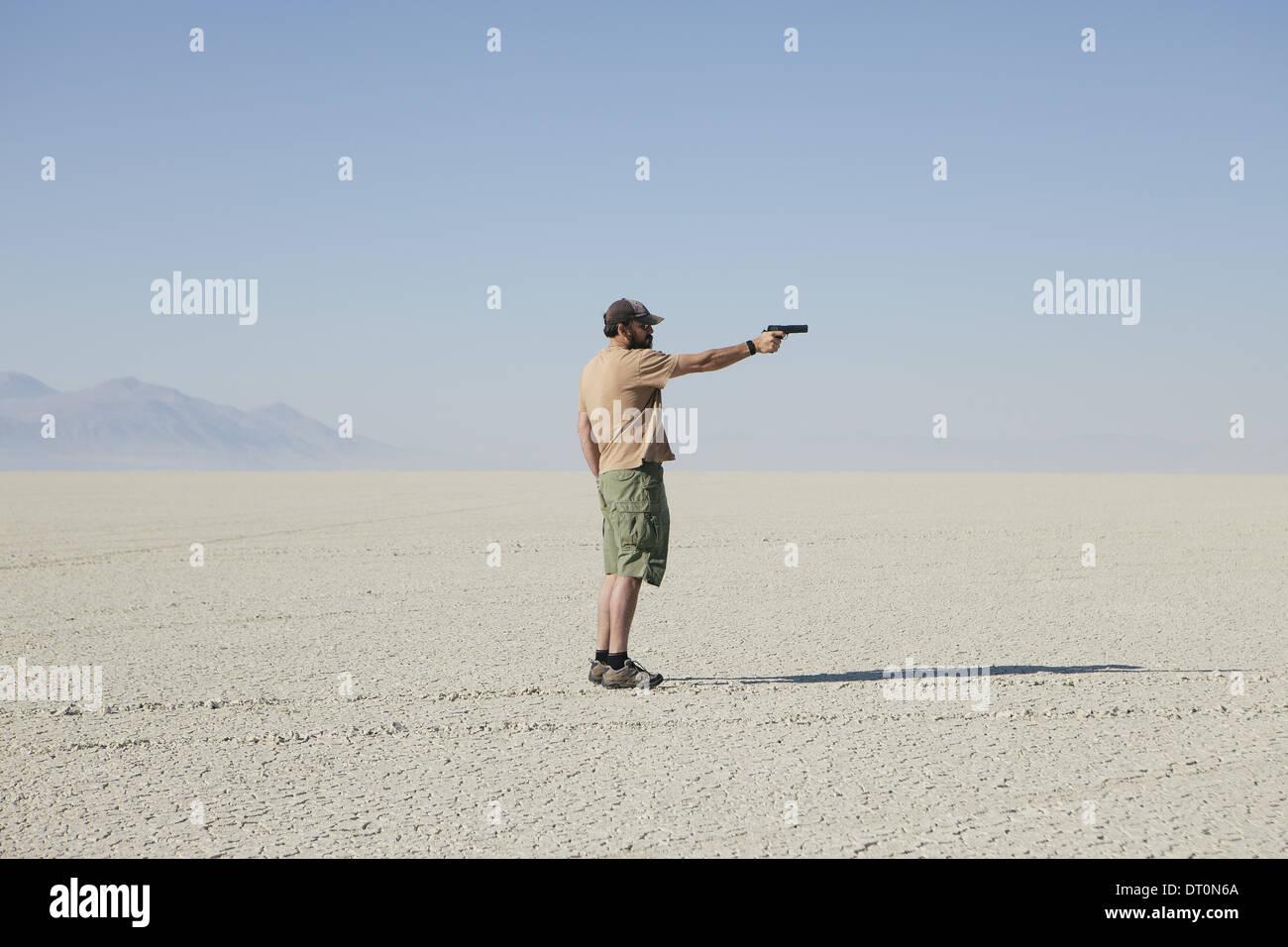 Black Rock Desert Nevada USA Man aiming hand gun standing in vast barren desert - Stock Image