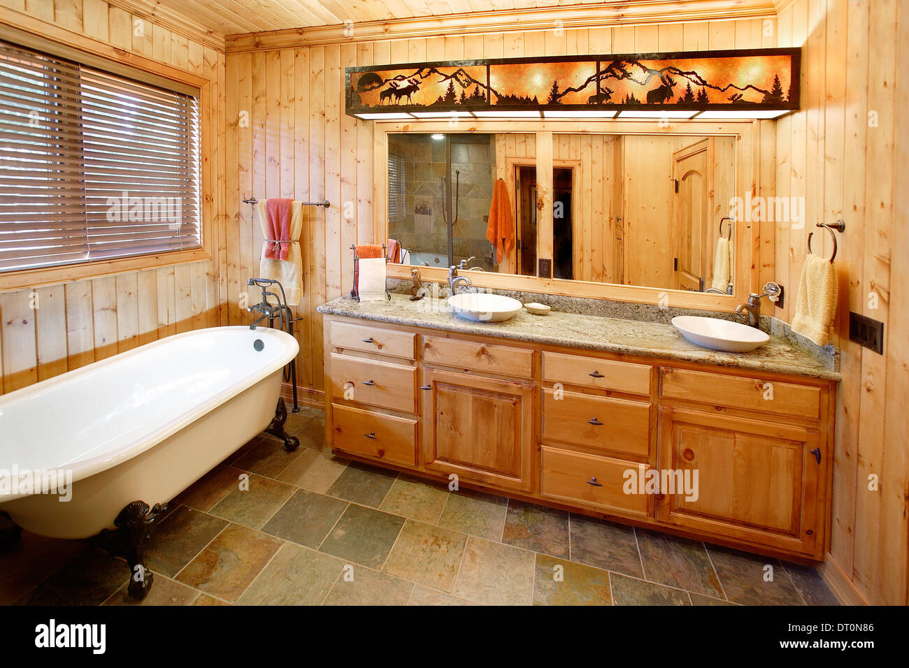 The master bath in a rustic mountain cabin. The room features a claw ...