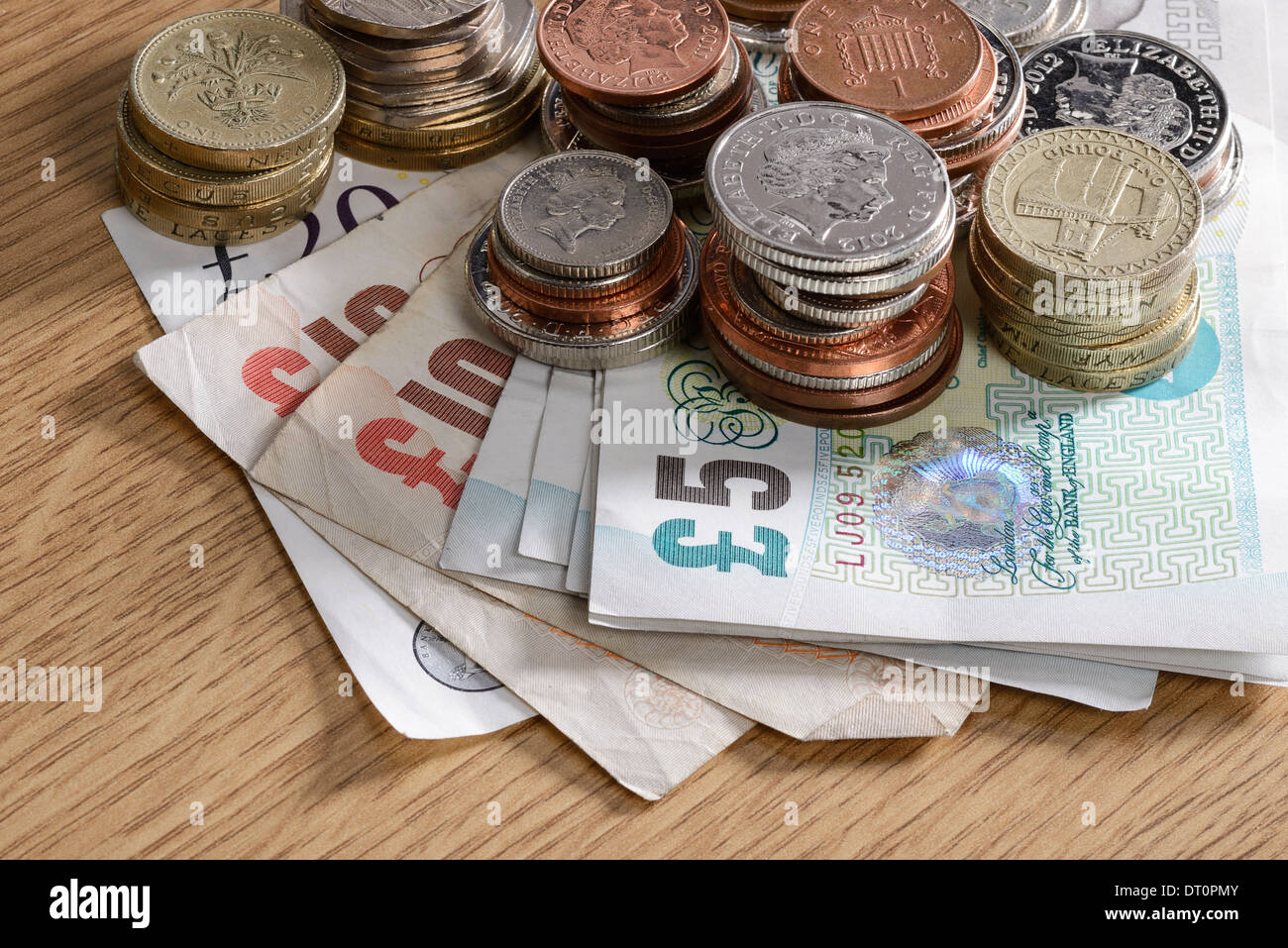 Pile of UK sterling cash notes and coins - Stock Image