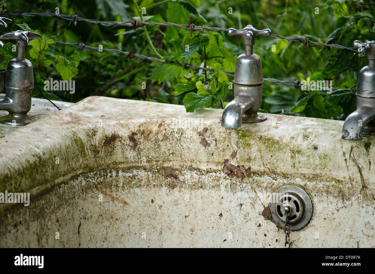 Detail of an old abandoned bath and taps - Stock Image