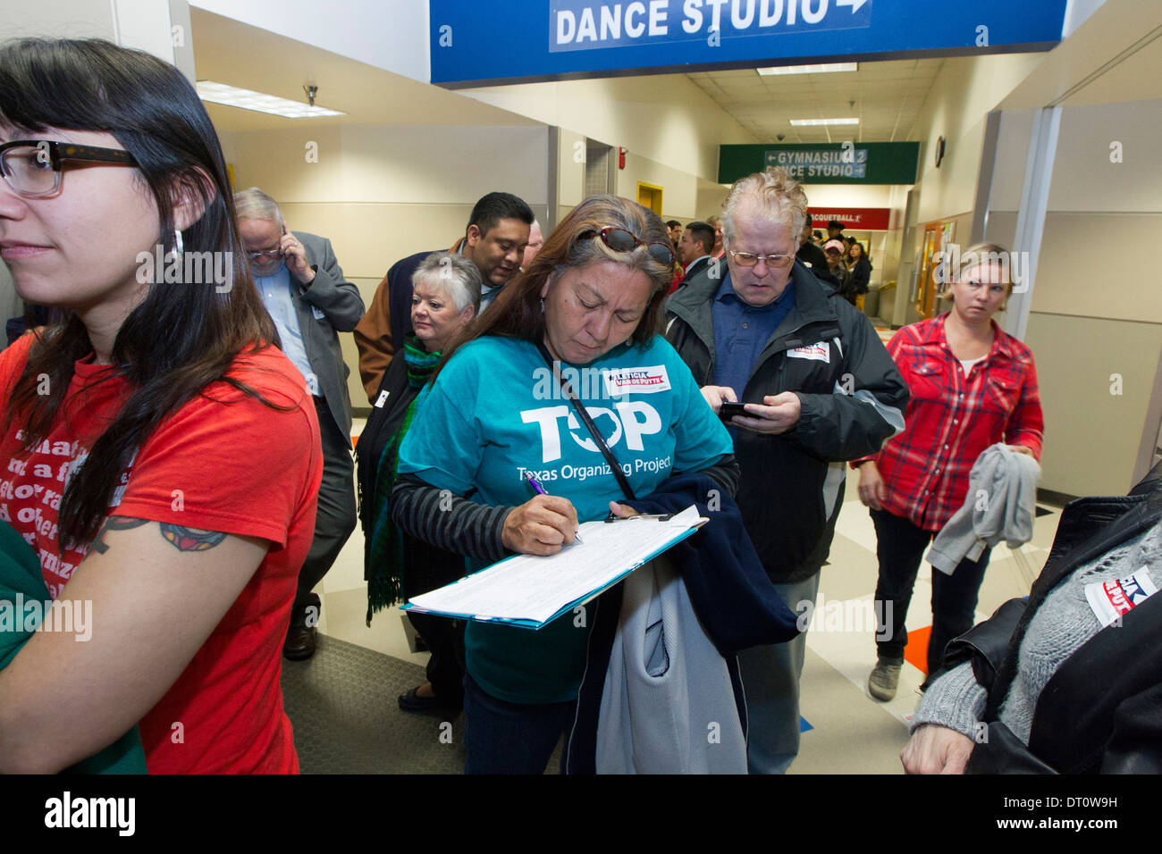 woman signs petition while waiting in line to attend political rally in San Antonio - Stock Image