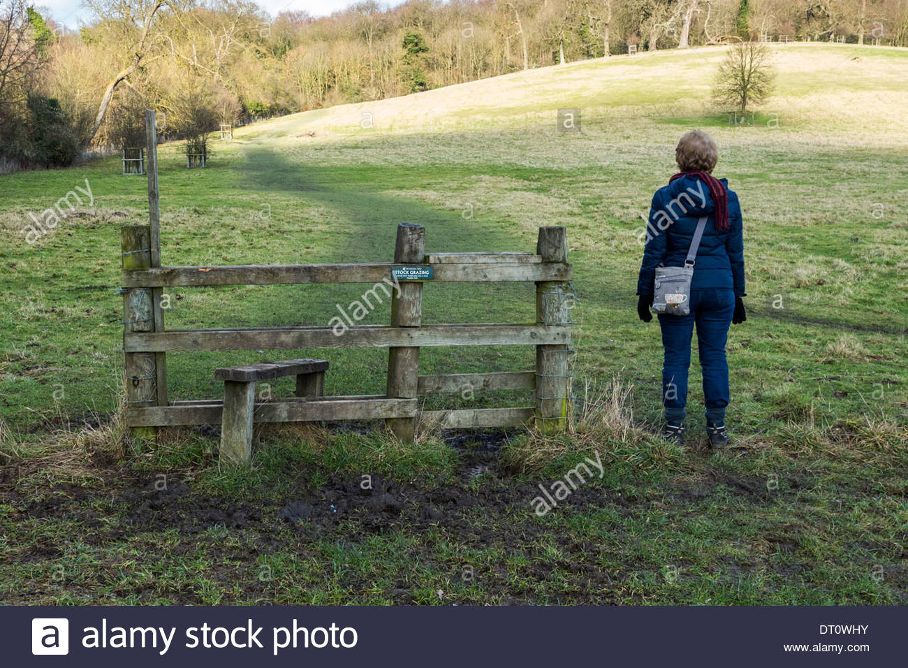 A walker bypasses a redundant stile on a footpath where the fence either side has been removed leaving it isolated - Stock Image