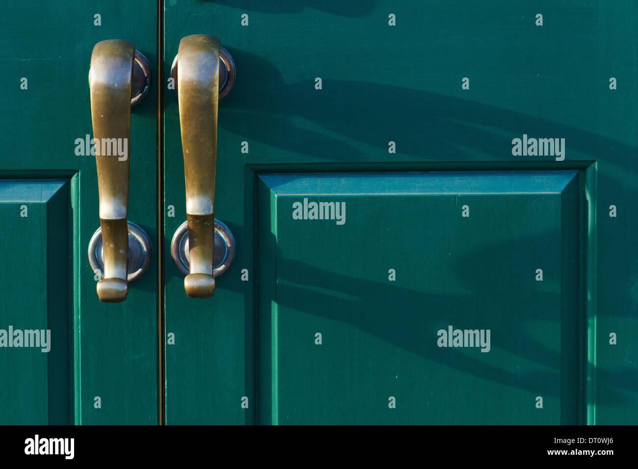 Bronze handles cast shadows on the green door - Stock Image