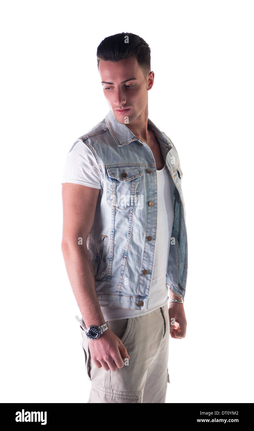 Attractive young man with jeans gilet (vest) and white t-shirt and pants. - Stock Image
