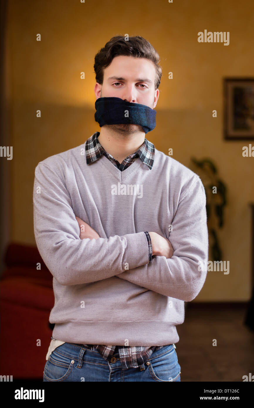 Young man with gag (scarf) on his mouth cannot speak - Stock Image