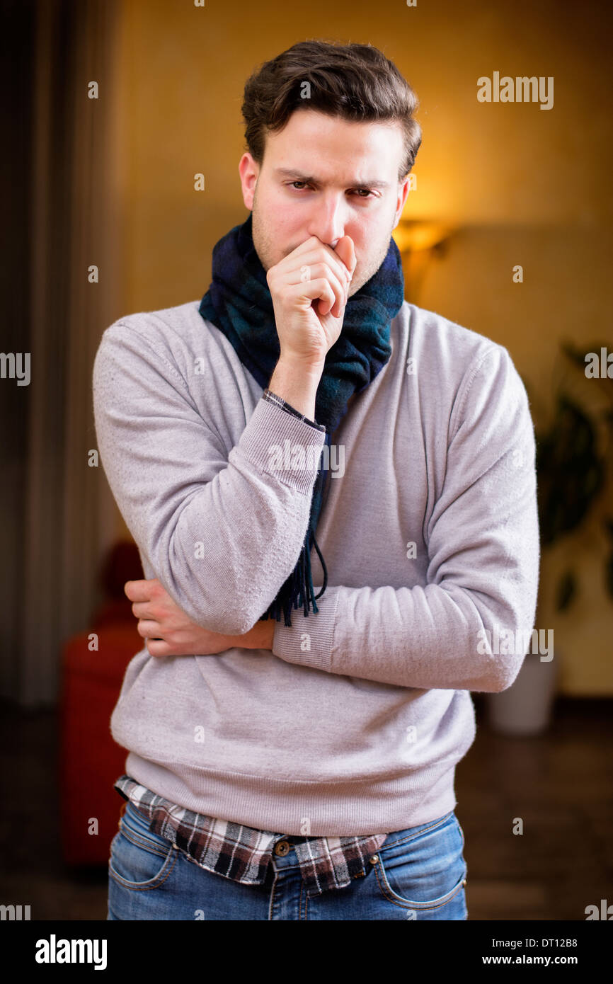 Young man at home sick, coughing, with hand in front of his mouth - Stock Image