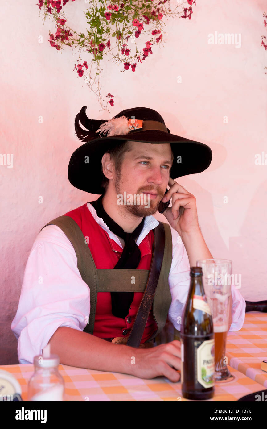 Young man using cellphone at beer festival in the village of Klais in Bavaria, Germany - Stock Image