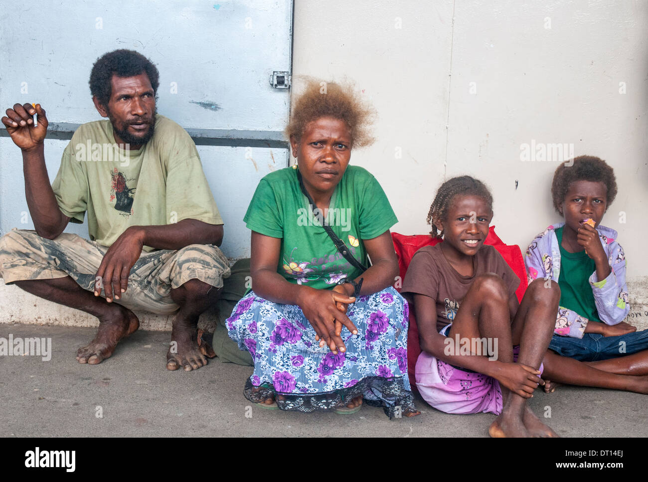 Solomon Islander family waiting for transport home from the Central Market in Honiara - Stock Image