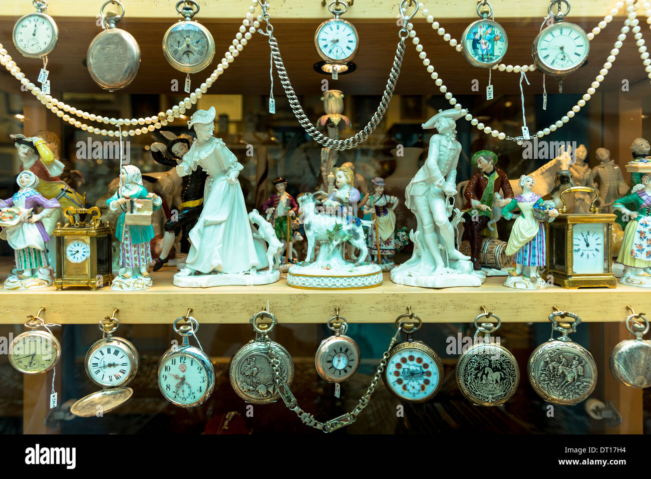 Porcelain figures, clocks and pocket watches on display at Bordhin antique shop in Burgstrasse in Munich, Bavaria, Germany - Stock Image