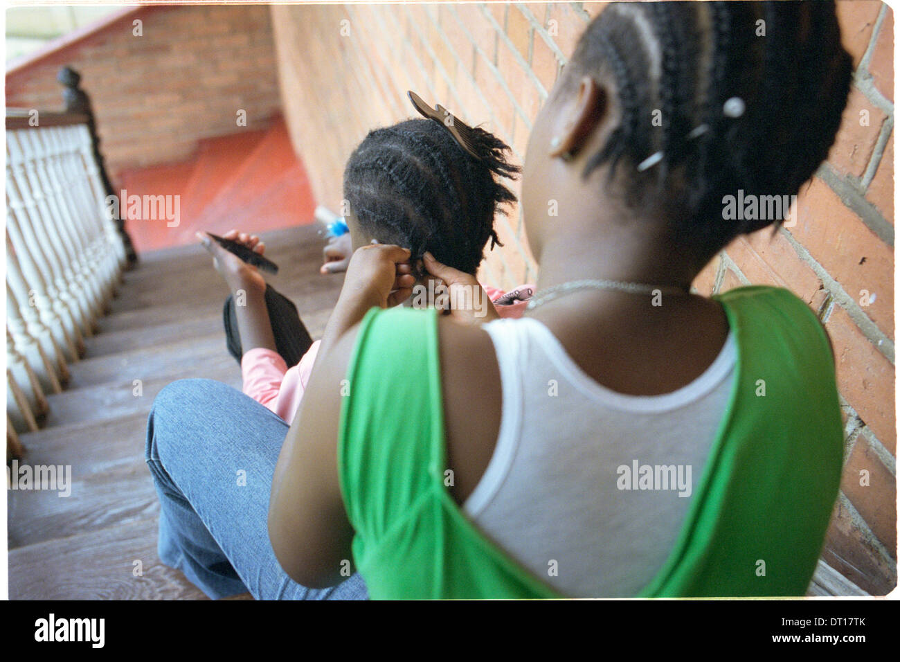 ipjr11049435 urban youth, programs, shelters two girls sit on steps as one braids the hair of her friend - Stock Image