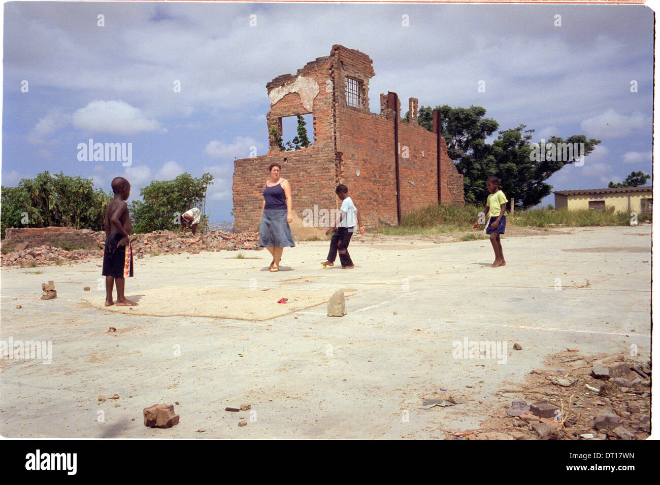 ipjr11041923 urban youth, programs, shelters western volunteer plays ball with children in kwamashu, kwazulu-natal south africa - Stock Image