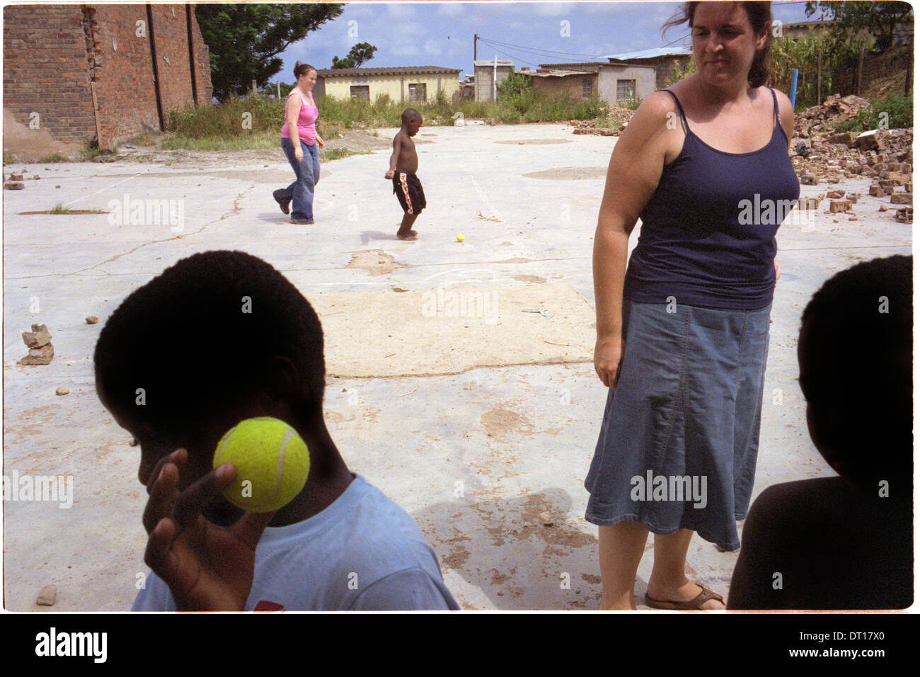 ipjr11041933 urban youth, programs, shelters western volunteer plays ball with children in kwamashu, kwazulu-natal south africa - Stock Image