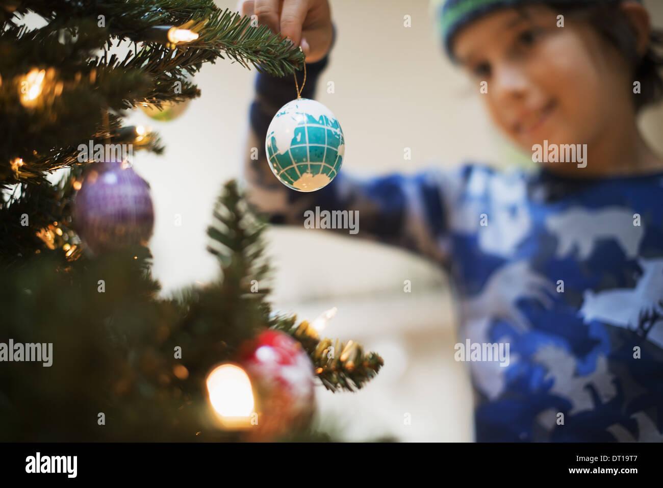 Woodstock New York USA boy placing Christmas ornaments on tree - Stock Image