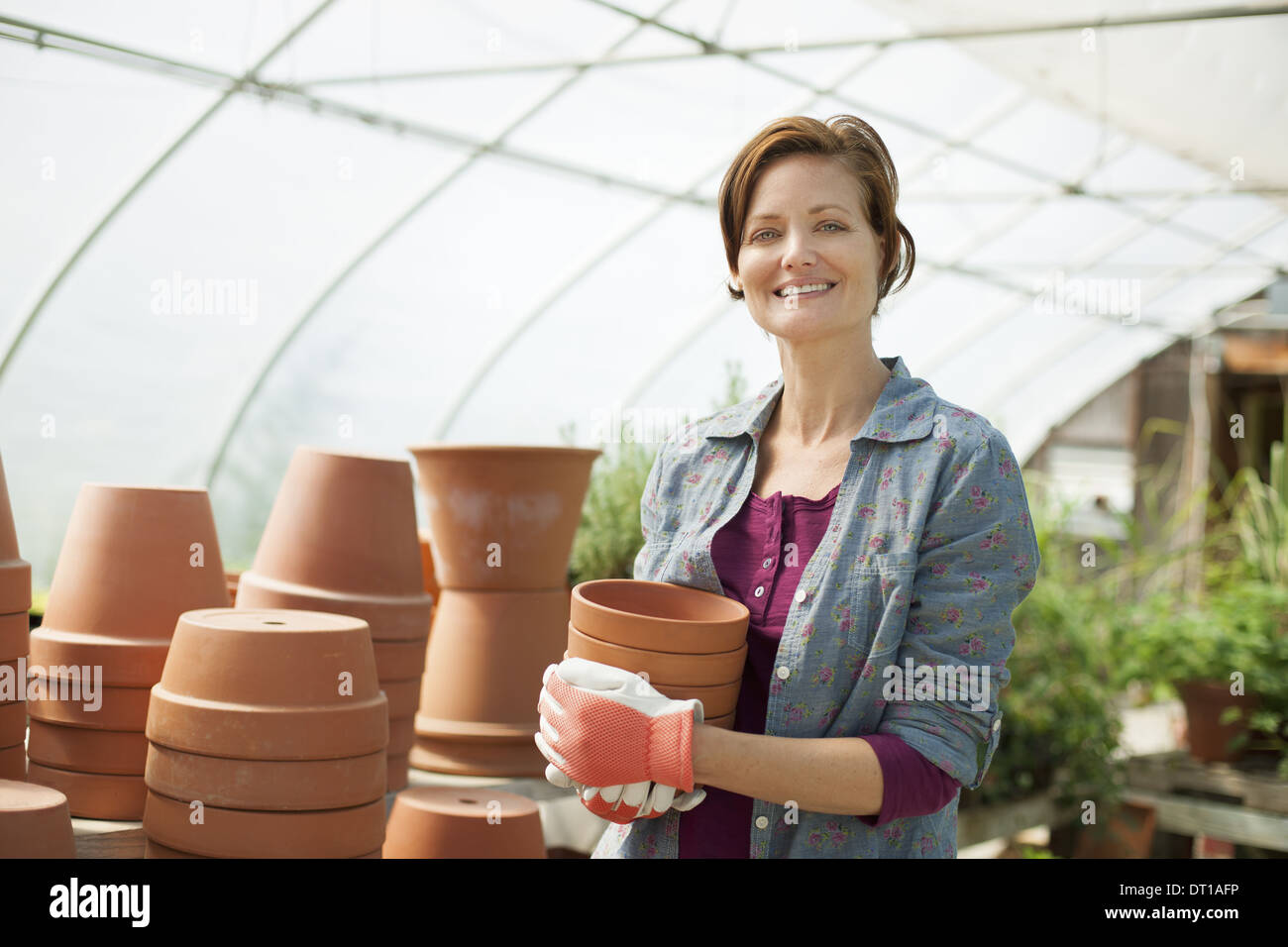 Woodstock New York USA woman wearing work gloves carrying terracotta pots - Stock Image