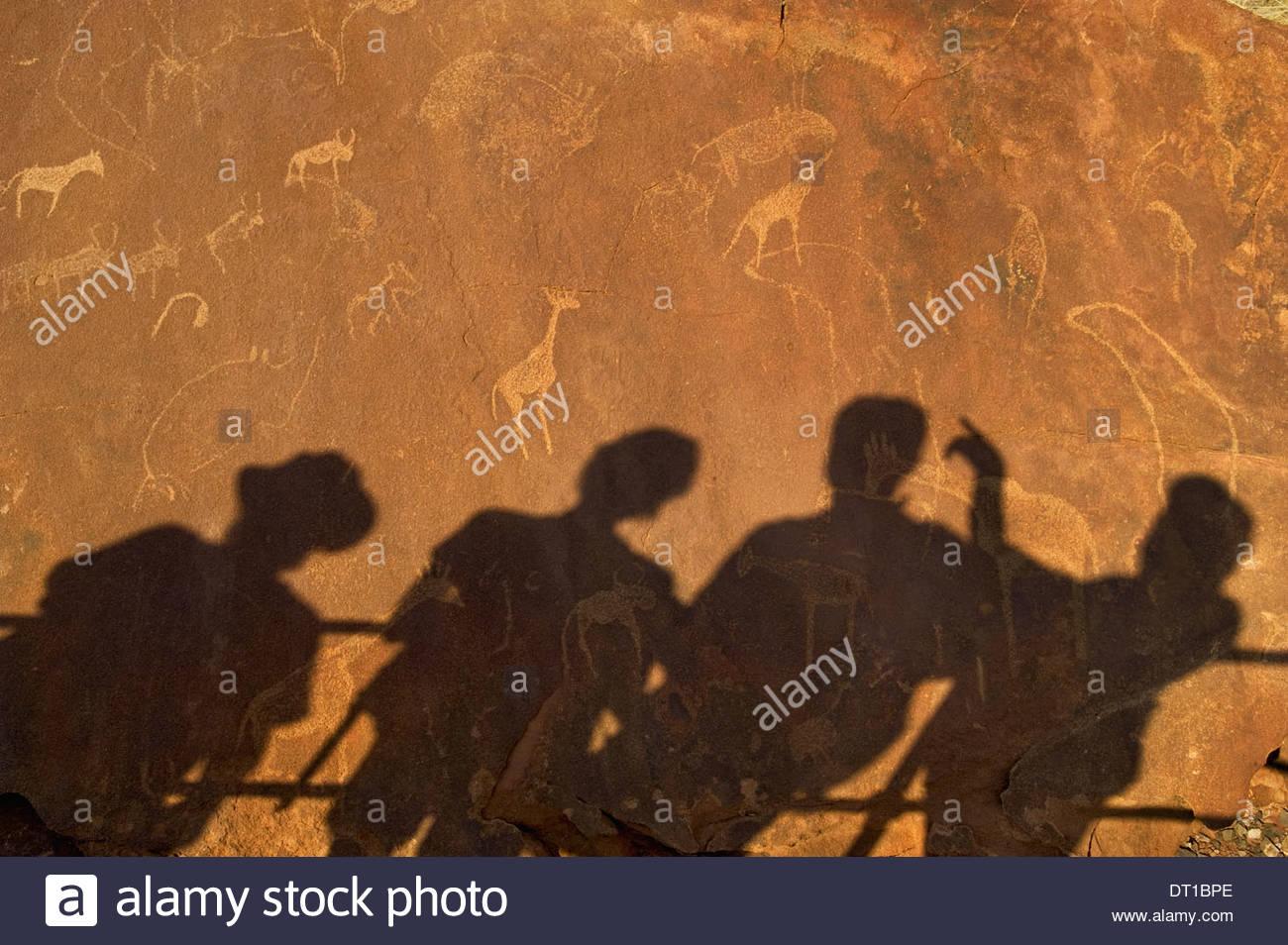 Uibasen Conservancy Damaraland Namibia. shadows tourists rock Twyfelfontein heritage site - Stock Image