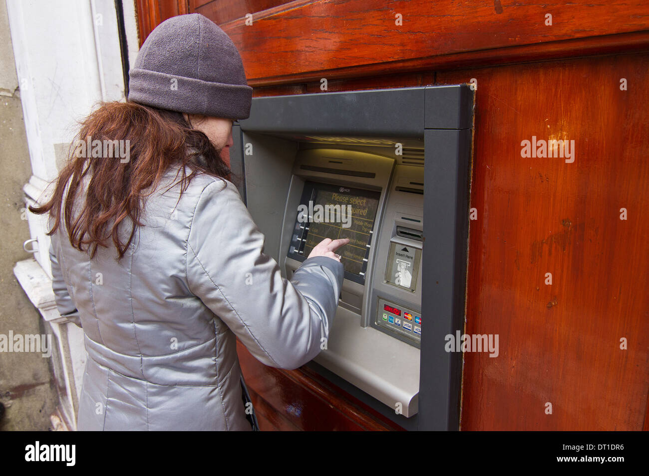 Woman using an ATM machine in Rochester Kent UK - Stock Image