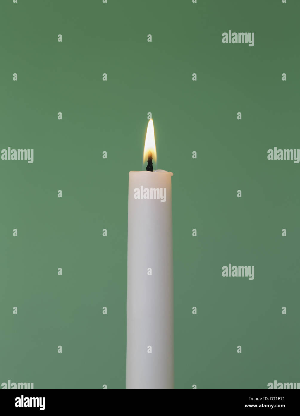 thin white wax candle with small lit flame - Stock Image