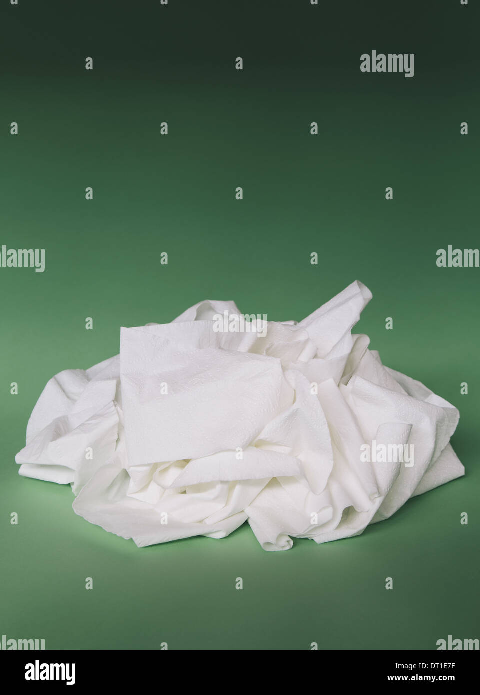 unwound toilet paper in heap on green background - Stock Image