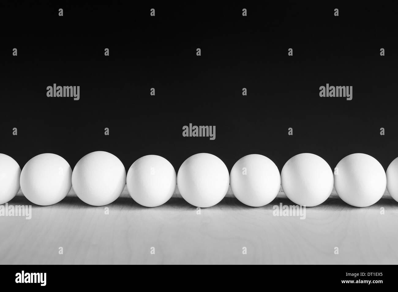 Row of white free range organic eggs black background - Stock Image