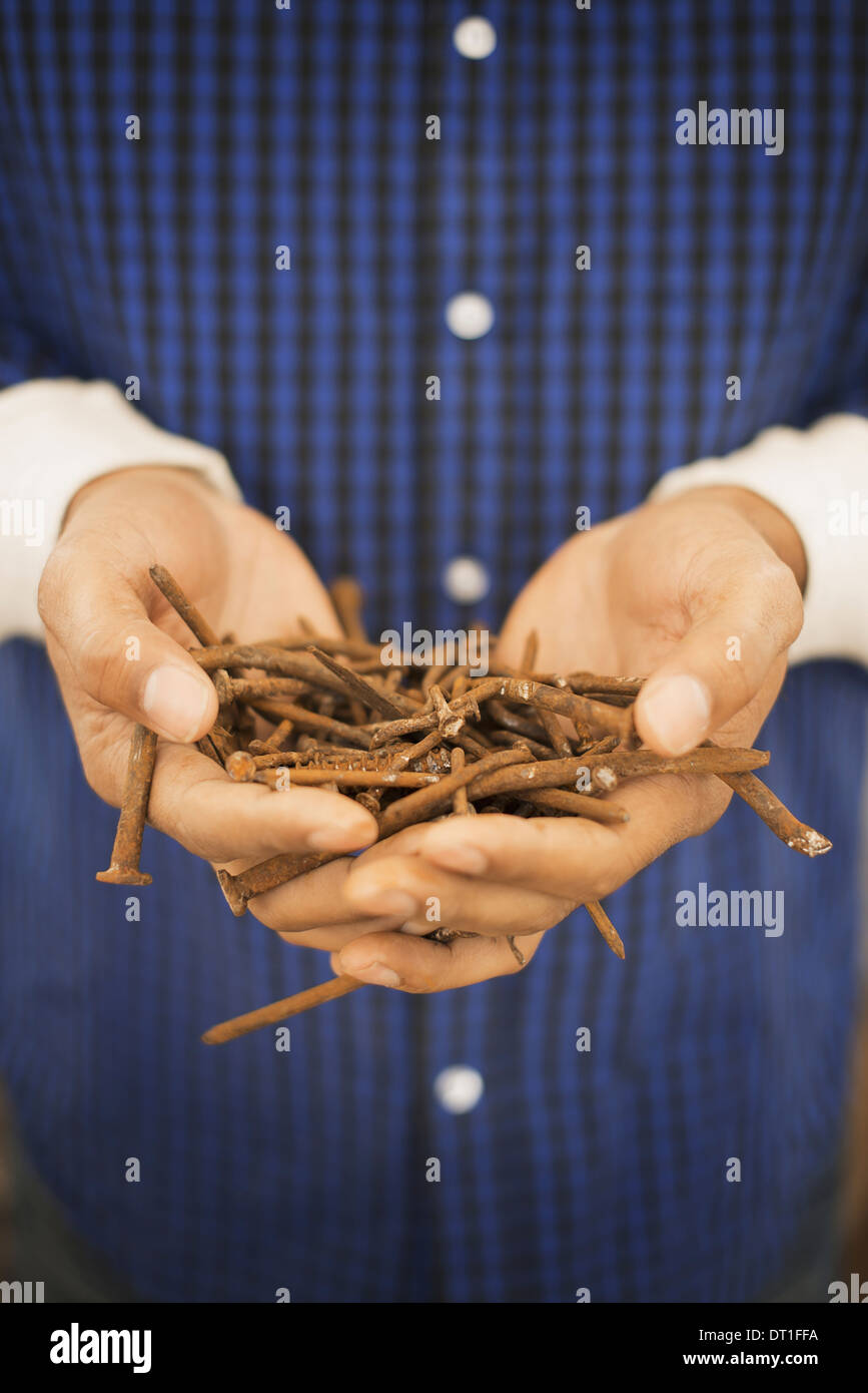 A person holding a heap of rusting metal nails taken from reclaimed timber - Stock Image