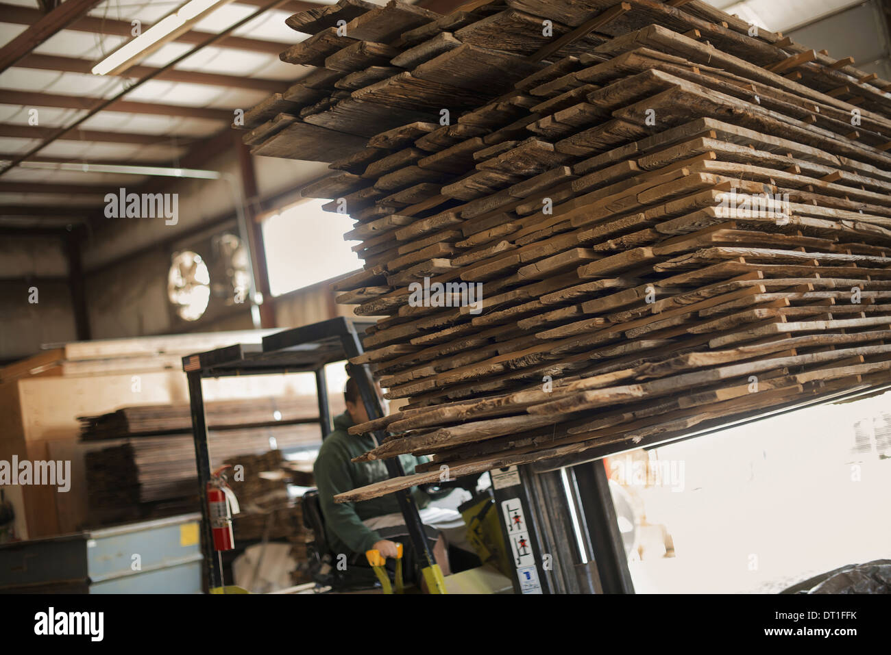A heap of recycled reclaimed timber planks of wood being moved on a forklift truck reclamation in a timber yard - Stock Image