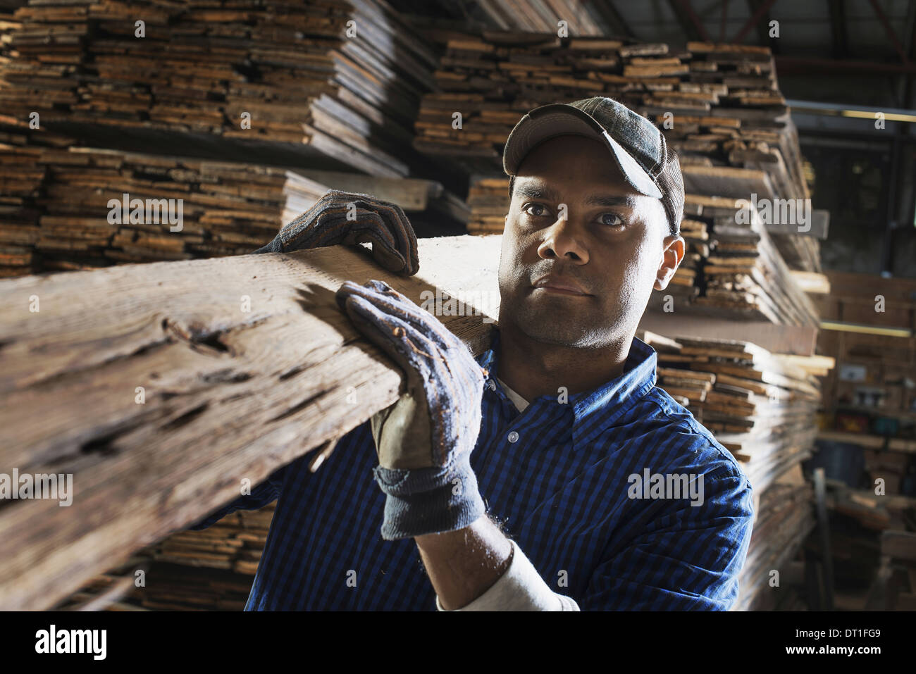 heap of recycled reclaimed timber planks of wood Environment timber yard A man carrying a large plank of splintered rough wood - Stock Image