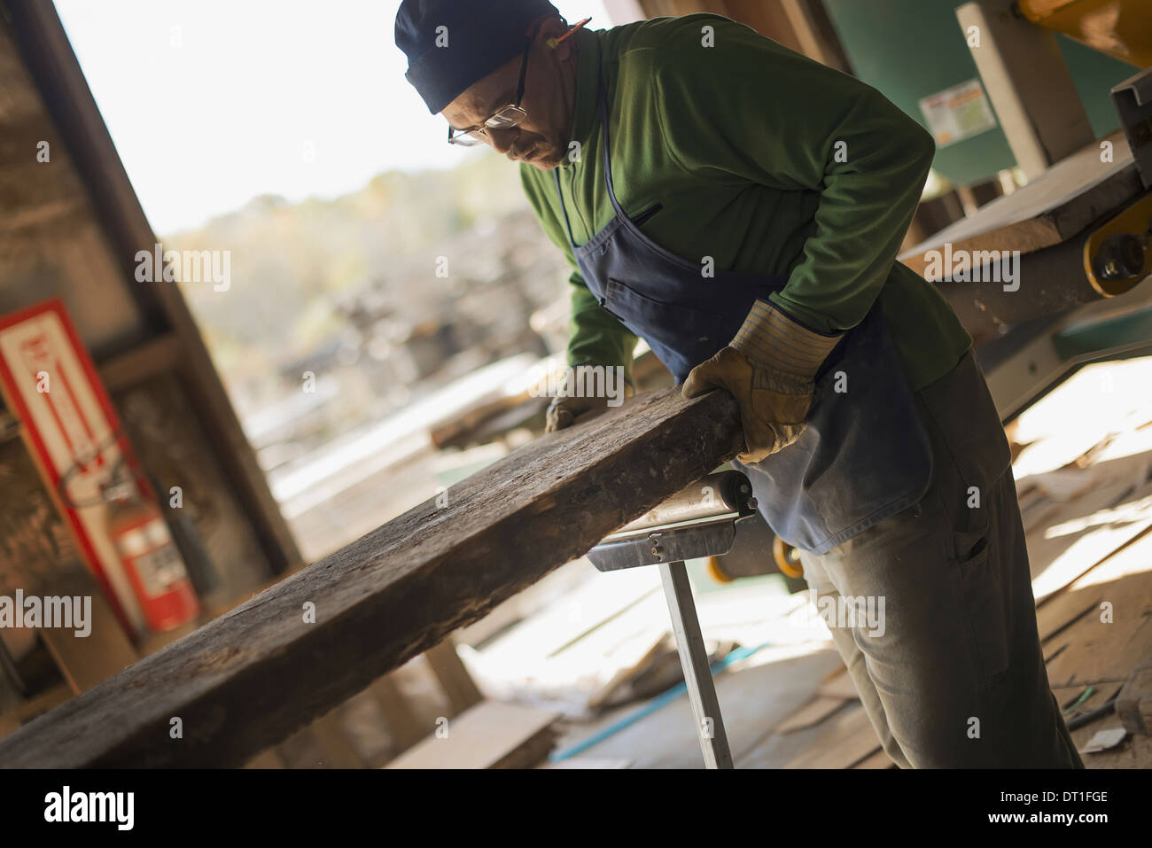 A man examining a large plank of cut wood in a reclaimed timber yard A workshop - Stock Image