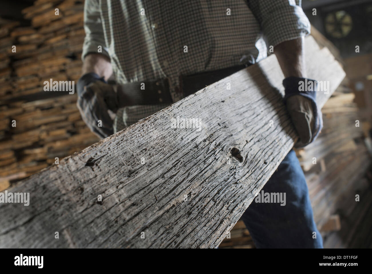A heap of recycled reclaimed timber planks of wood Environment A man carrying a large plank of mature weathered - Stock Image