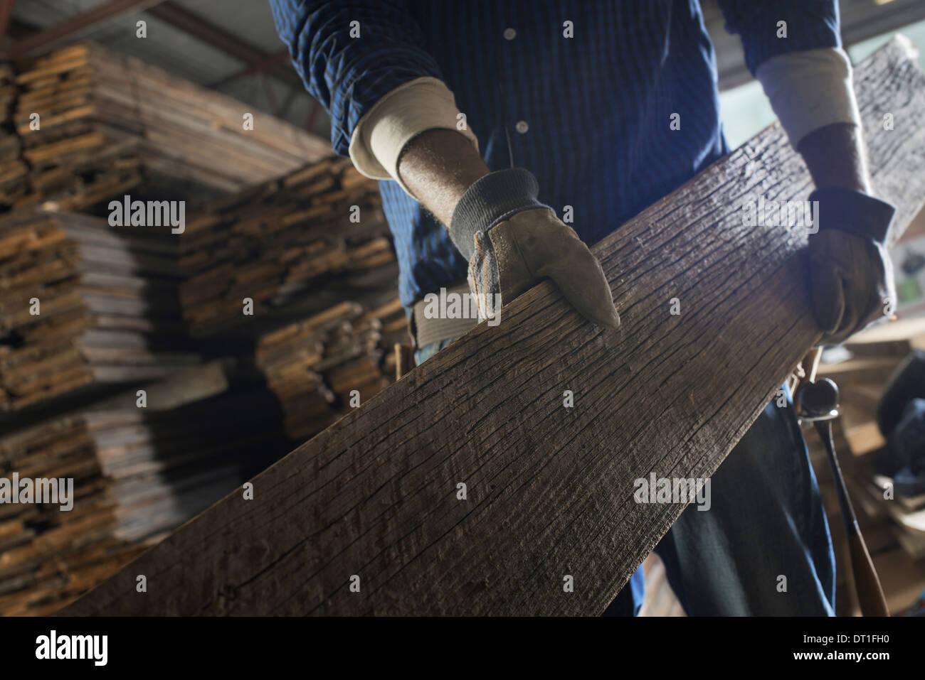 A heap of recycled reclaimed timber planks of wood in a timber yard A man carrying a large plank of wood - Stock Image