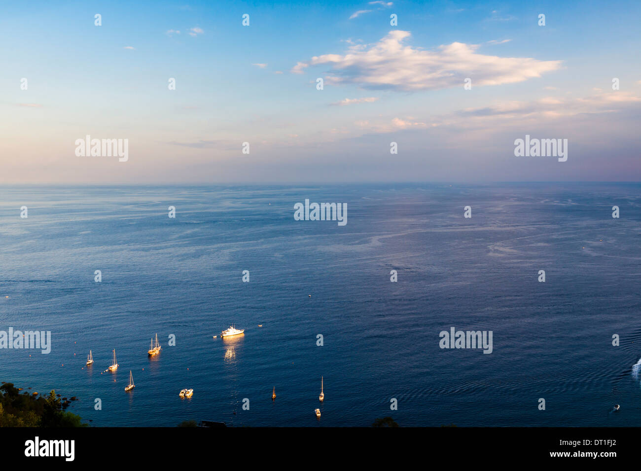 Boats on the Ionian Sea, part of the Mediterranean Sea at sunset, Taormina, East Coast of Sicily, Italy, Mediterranean, Europe - Stock Image