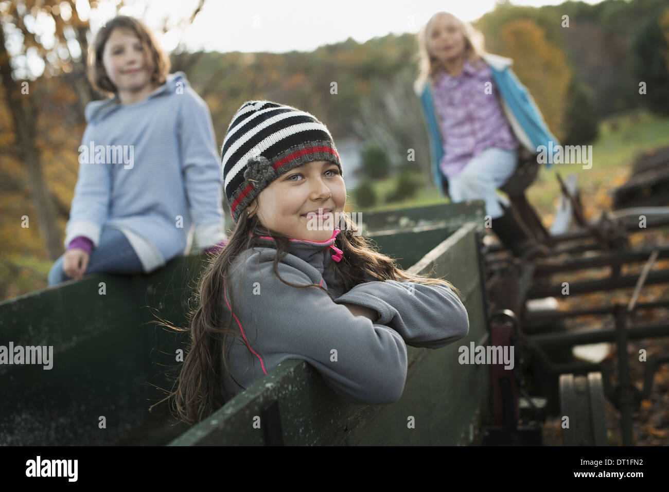 Three young girls out and about on the farm On an old trailer - Stock Image