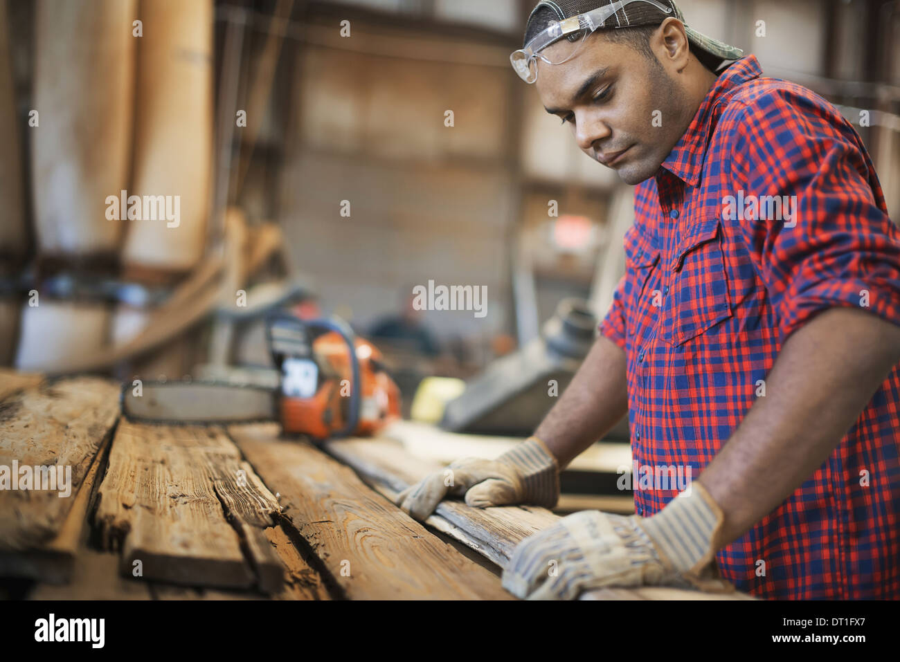 A reclaimed lumber workshop A man measuring and checking planks of wood for re-use and recycling - Stock Image
