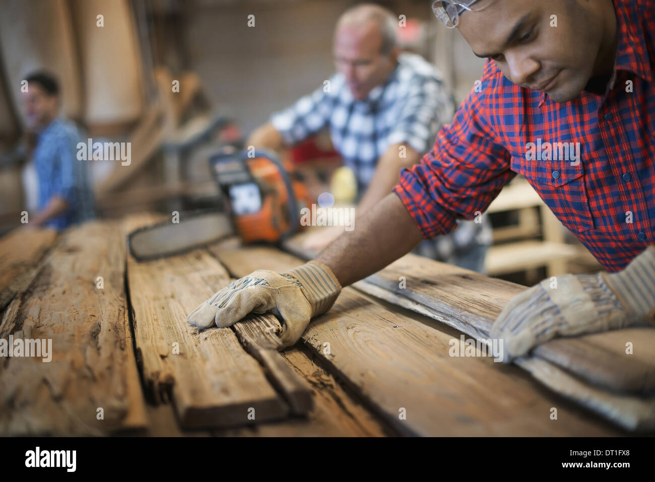 A reclaimed lumber workshop A group of people working A man measuring and checking planks of wood for re-use and recycling - Stock Image