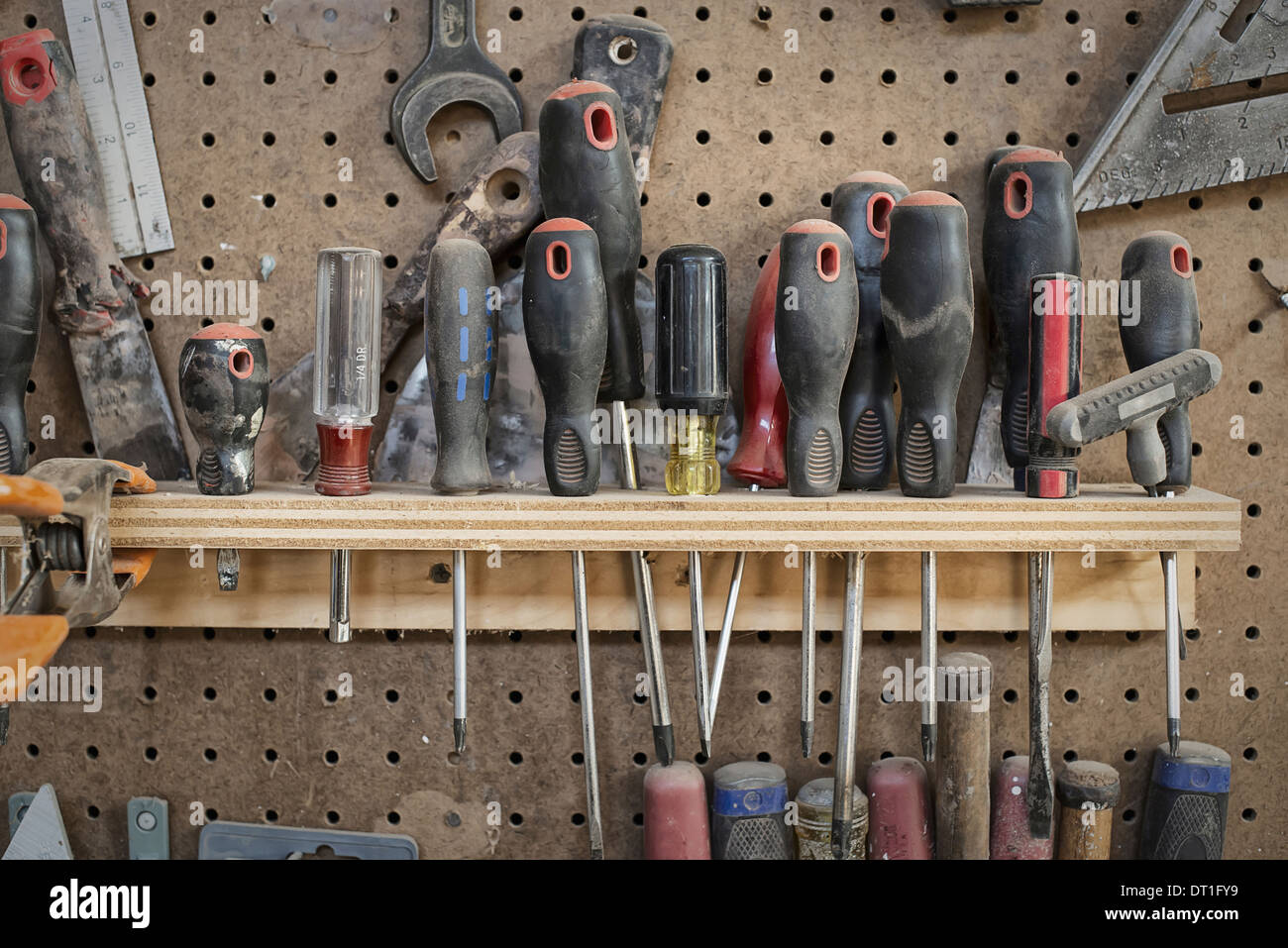 A reclaimed lumber workshop A tool board with slots for screwdrivers and handheld woodworking tools - Stock Image